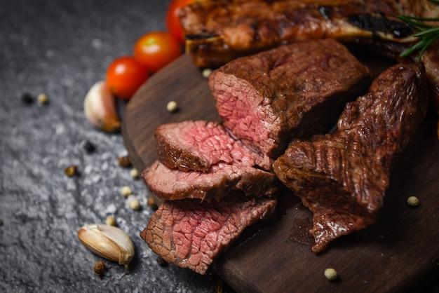 Filé de bife assado com ervas e especiarias, servido com vegetais na placa de madeira - fatia de carne grelhada na superfície preta Foto Premium