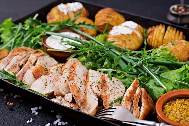 Filé de frango cozido em uma grelha com um enfeite de batatas assadas. refeição dietética. comida saudável. Foto gratuita