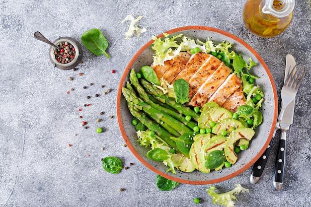 Filé de frango cozido em uma grelha com uma guarnição de aspargos e avokado grelhado. cardápio dietético. Foto Premium