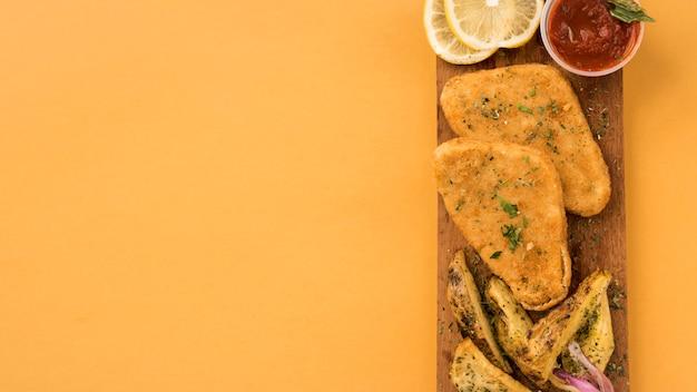 Filé de frango empanado e fatias de batata na tábua de madeira Foto gratuita