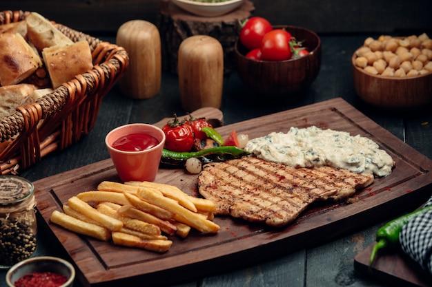 Filé de frango grelhado com molho cremoso de cogumelos, batata frita e ketchup Foto gratuita