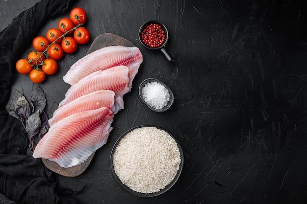 Filé de peixe branco, com ingredientes de arroz basmati e tomate cereja, na mesa preta, vista de cima Foto Premium