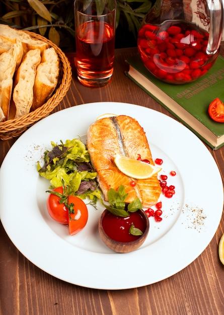 Filé de peixe grelhado salmão branco com salada verde, tomate, limão e molho vermelho mergulho em chapa branca Foto gratuita