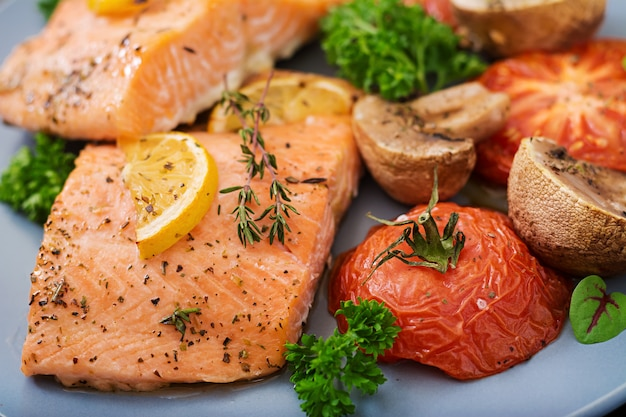 Filé de peixe salmão assado com tomates, cogumelos e especiarias. menu de dieta. Foto gratuita