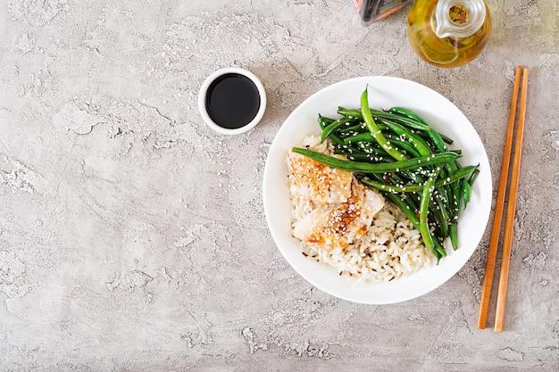 Filé de peixe servido com arroz, molho de soja e feijão verde em chapa branca. comida asiática. vista do topo. configuração plana Foto Premium