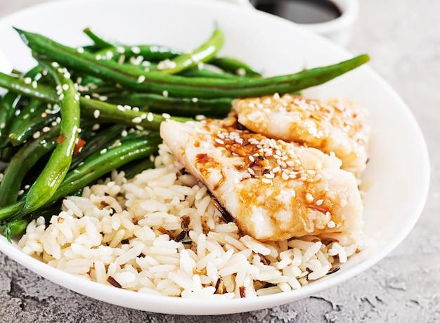 Filé de peixe servido com arroz, molho de soja e feijão verde em chapa branca. comida asiática. Foto Premium