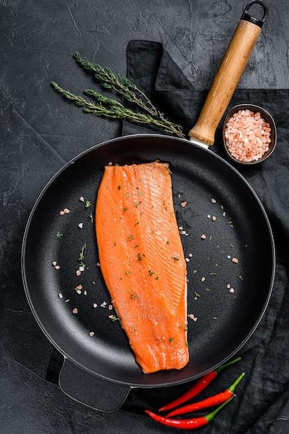 Filé de salmão cru com sal e pimenta em uma panela. peixe orgânico Foto Premium