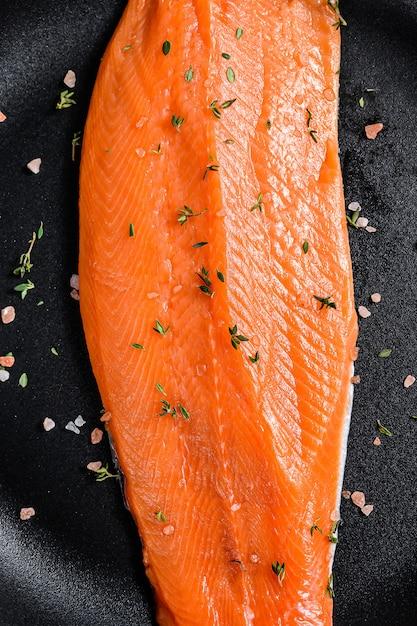 Filé de salmão cru com sal e pimenta em uma panela. peixe orgânico. Foto Premium