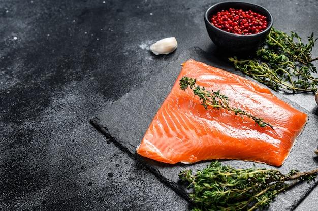 Filé de salmão cru fresco com tomilho em preto. vista do topo. copie o espaço Foto Premium