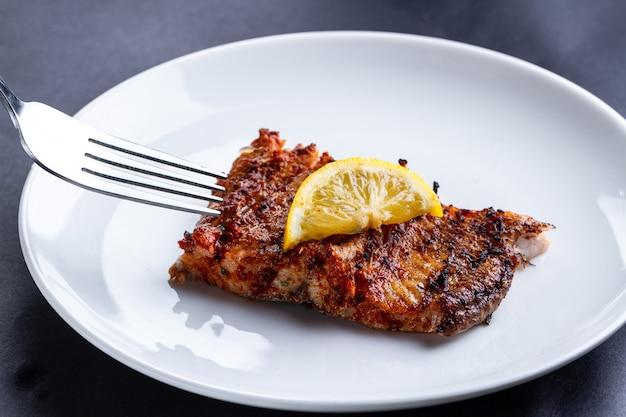 Filé de salmão fresco e grelhado com uma fatia de limão suculento em um prato branco Foto Premium