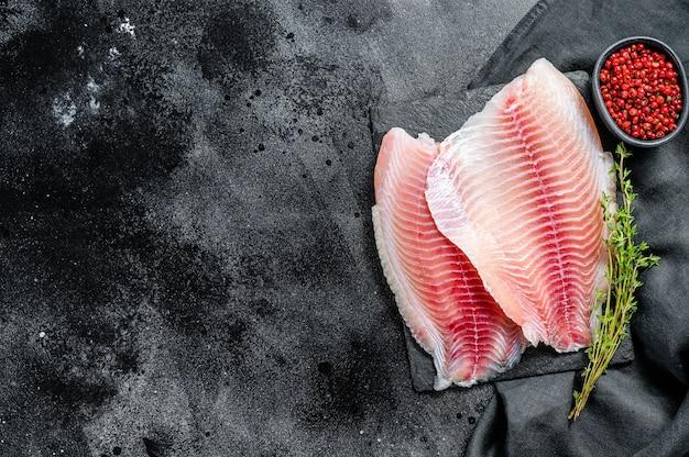 Filé de tilápia cru em uma tábua de cortar com tomilho e pimenta rosa. fundo preto. vista do topo. copie o espaço. Foto Premium