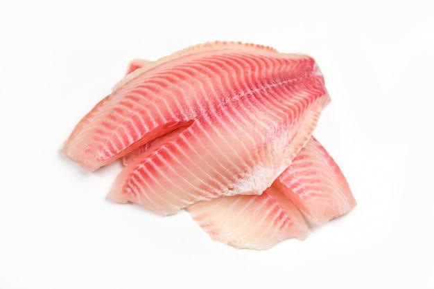 Filé de tilápia cru peixe isolado no fundo branco para cozinhar alimentos - filé de peixe fresco fatiado para bife ou salada Foto Premium