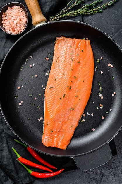 Filé de truta crua com sal e pimenta em uma panela. peixe orgânico. superfície preta. vista do topo. Foto Premium