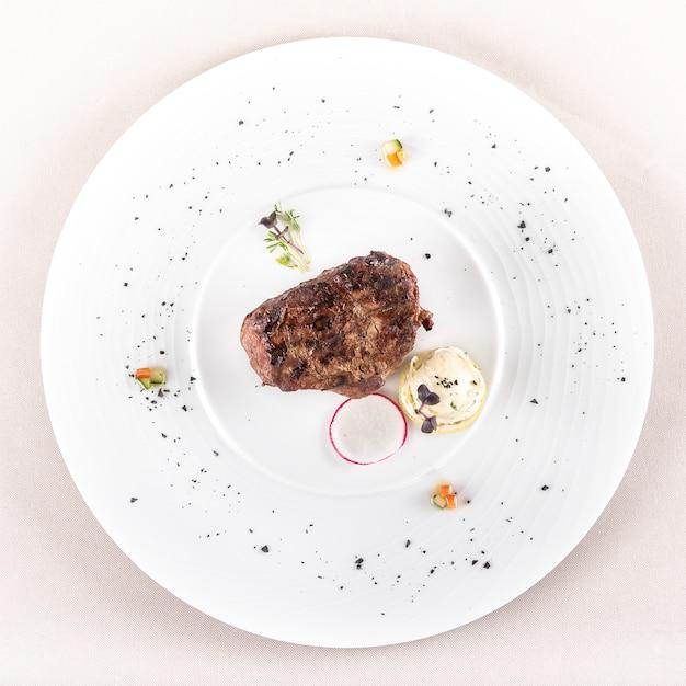 Filé mignon suculento, servido com manteiga e ervas, decorado com rabanete Foto Premium