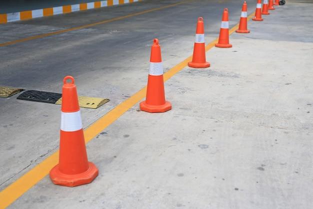 Fileira do cone de borracha alaranjado do tráfego colocado na estrada. | Foto Premium