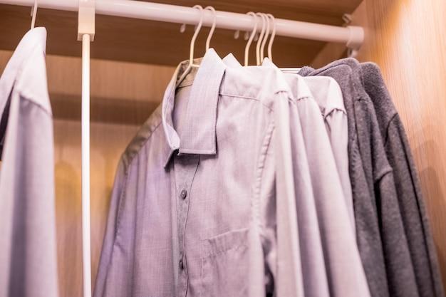 Fileira dos ternos dos homens que penduram no closet.buy e vendem, homem de negócio. armário do homem. Foto Premium