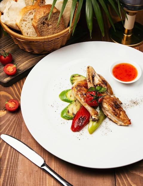 Filés de frango grelhado, assado e legumes em chapa branca com molho Foto gratuita