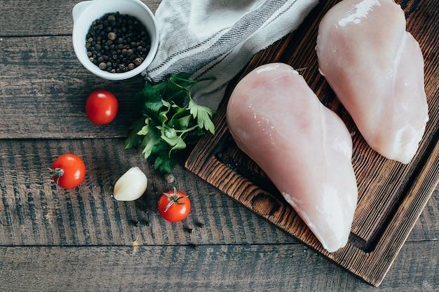 Filés de peito de frango cru e ingredientes para o jantar na placa de madeira no fundo da tabela Foto Premium