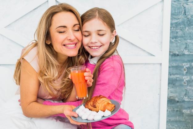 Filha abraça mãe com café da manhã na cama Foto gratuita