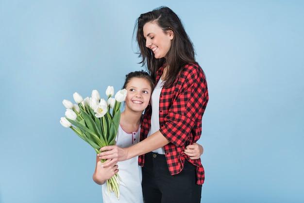 Filha, abraçando, mãe, e, dar, dela, tulips Foto gratuita