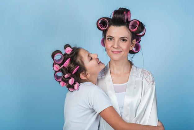 Filha, abraçando, mãe, em, curlers, e, bathrobe Foto gratuita