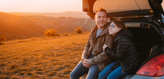 Filha, abraçando o pai enquanto está sentado em uma mala de carro Foto Premium