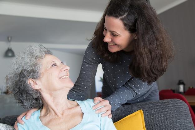Filha adulta feliz visitando a mãe idosa Foto gratuita