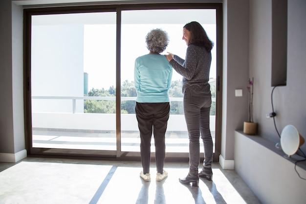 Filha alegre mostrando a mãe seu novo apartamento Foto gratuita