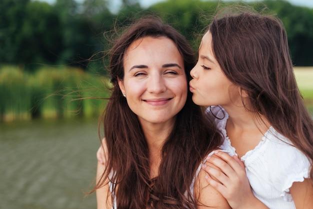 Filha, beijando, feliz, mãe, por, a, lago Foto gratuita