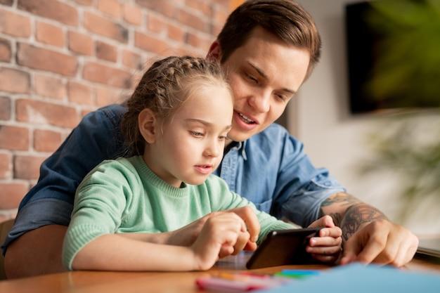 Filha curiosa contente com cabelos trançados sentada à mesa e jogando videogame no telefone enquanto o pai explica como completar o nível Foto Premium