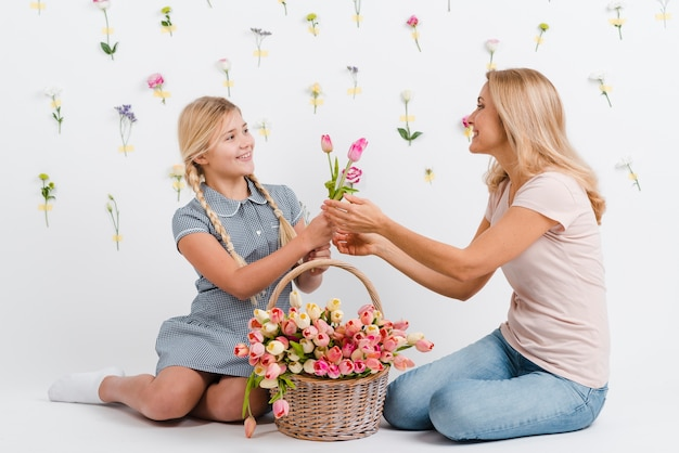 Filha dando para mãe flores Foto gratuita