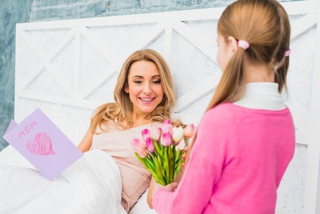 Filha dando tulipas para a mãe na cama Foto gratuita