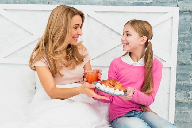Filha, dar, croissant, ligado, prato, para, mãe, cama Foto gratuita