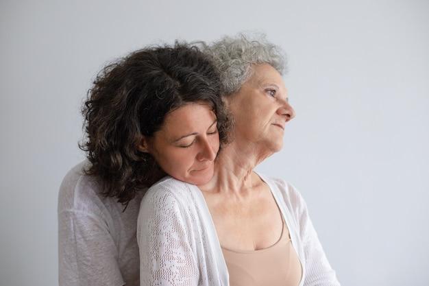 Filha de meia idade, abraçando a mãe sênior Foto gratuita