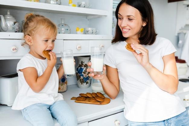 Filha e mãe bebendo leite e comendo biscoitos Foto gratuita