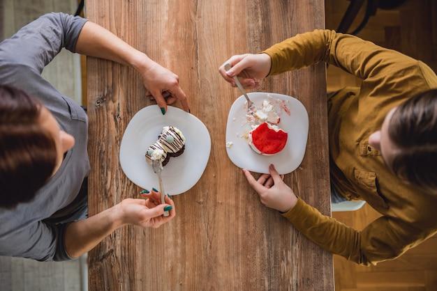 Filha e mãe comendo bolo em casa Foto Premium