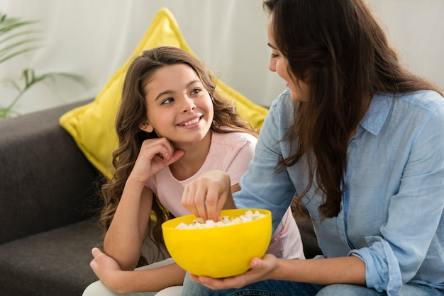Filha e mãe comendo pipoca juntos Foto gratuita
