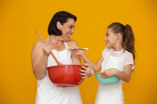 Filha e mãe preparando uma receita Foto Premium