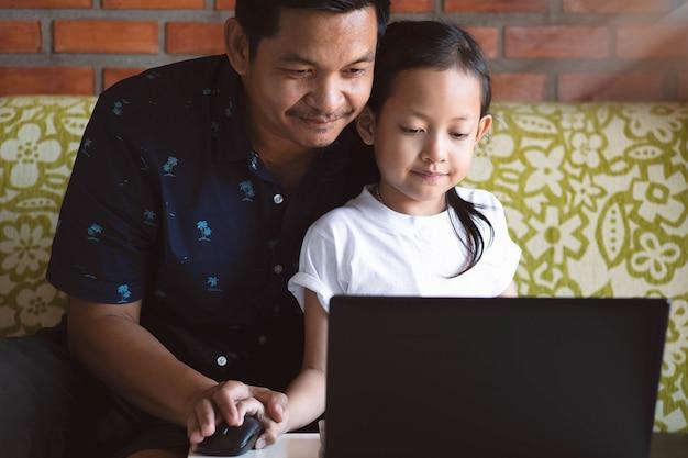Filha e pai aprendendo e jogando computador portátil em casa Foto Premium