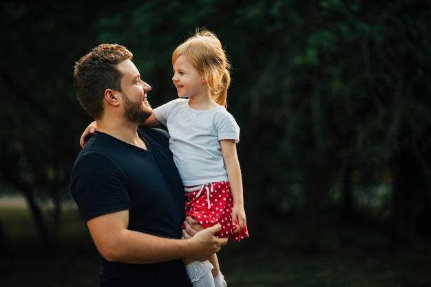 Filha e pai sorrindo um para o outro Foto gratuita