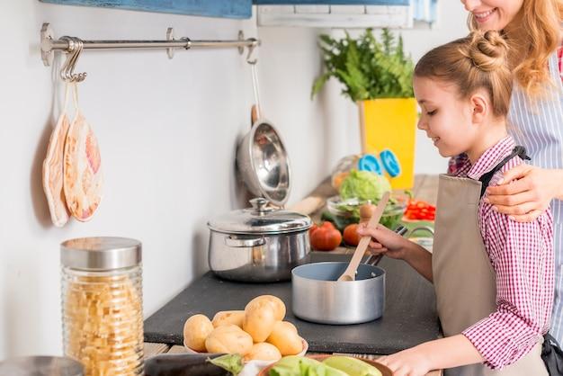 Filha e sua mãe cozinhar sopa na cozinha Foto gratuita