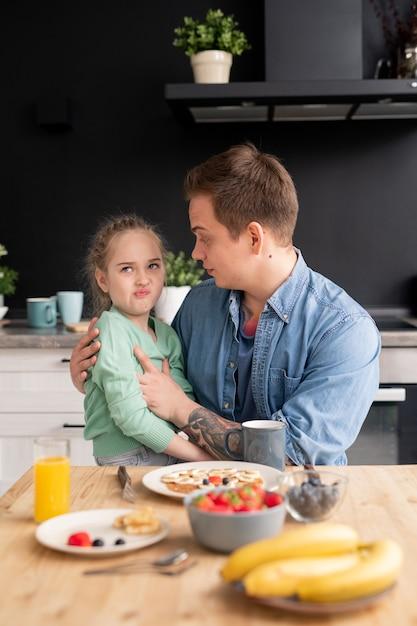 Filha exigente sentada nos joelhos do pai fazendo careta enquanto se recusa a comer o café da manhã feito pelo pai Foto Premium