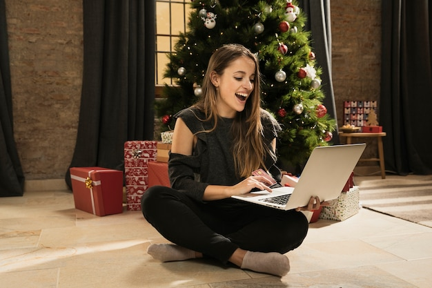 Filha feliz orgulhosa de seu laptop Foto gratuita