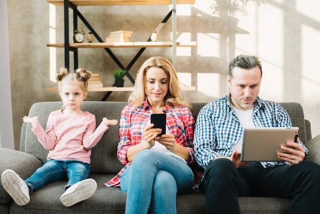 Filha irritada sentado no sofá com a mãe e o pai usando tablet digital; celular em casa Foto gratuita