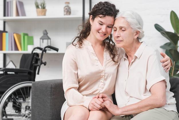 Filha jovem sentado no sofá abraçando sua mãe Foto gratuita