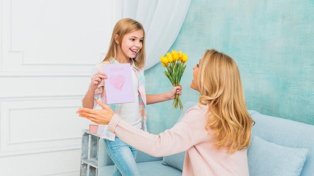 Filha, mostrando, presentes, flores, e, mother`s, dia, cartão postal, para, mãe Foto gratuita