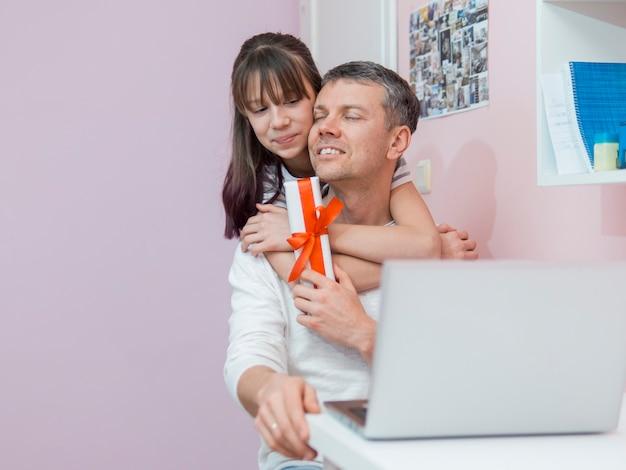 Filha oferece um presente e abraços ao pai Foto gratuita