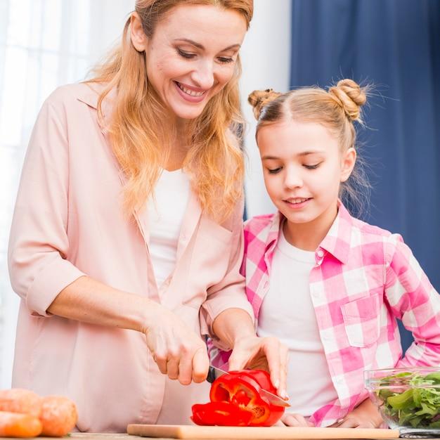 Filha, olhar, dela, mãe, corte, a, vermelho, pimentas sino, com, faca, ligado, tábua cortante Foto gratuita