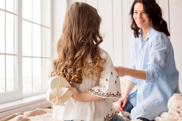Filha, segurando, caixa presente, atrás de, costas, para, mãe Foto gratuita
