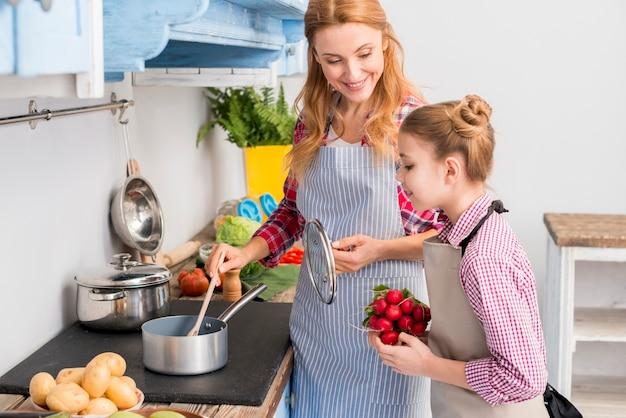 Filha, segurando, nabo, mão, olhar, dela, mãe, preparar, alimento, cozinha Foto gratuita